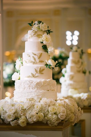 wedding-cake-white-with-ruffles-flower-layers-gold-leaves-fresh-roses-greenery