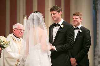 bride-and-groom-recite-vows-at-catholic-ceremony