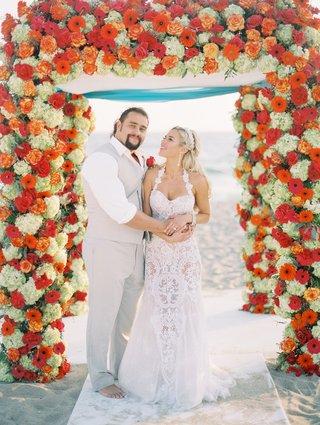 cj-lana-perry-and-miroslav-rusev-barnyashev-on-wedding-day-under-arch-barefoot-groom-beach
