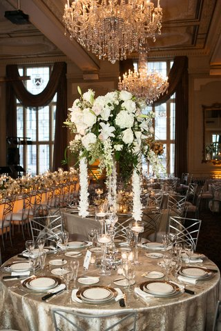 silver-linens-centerpiece-with-large-white-flowers-and-cascading-garland-of-orchids