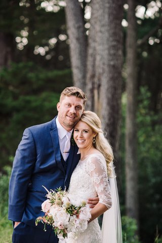 bride-in-oleg-cassini-dress-with-navy-blue-groom-in-forest