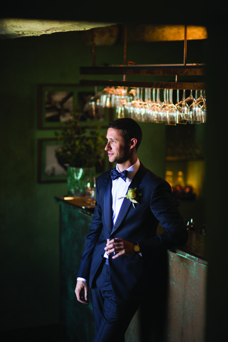 groom-in-navy-armani-suit-and-matching-bow-tie-leans-against-bar