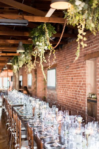 brick-wall-wedding-reception-decor-suspended-greenery-arrangements-wood-table-chairs-white-cushions