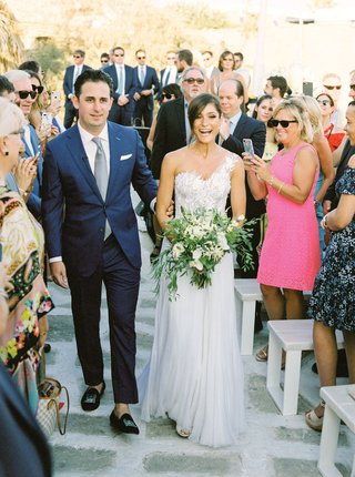 bride-in-one-shoulder-mira-zwillinger-wedding-dress-carines-bridal-atelier-with-groom-in-blue-suit