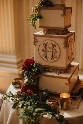 wedding-cake-square-rectangular-layers-with-gold-monogram-greenery-red-burgundy-flowers-candlelight