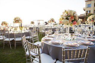 wedding-reception-on-grass-lawn-in-mexico-with-grey-linens-white-and-coral-centerpieces-crystals