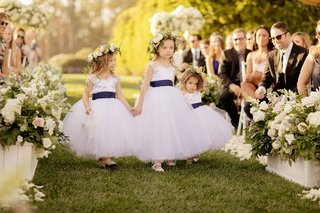 flower-girls-holding-hands-walking-down-grass-aisle-flower-crown-blue-sashes-gerrit-cole-wedding