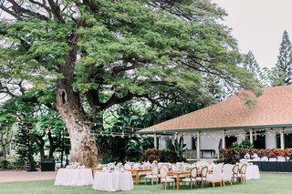 wedding-reception-venue-outdoor-plantation-lawn-string-lights-wood-tables-and-chairs