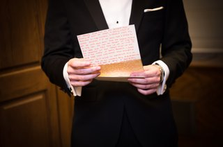 groom-in-bonobos-tux-reads-handwritten-letter-from-bride