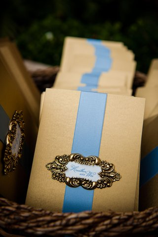 gold-ceremony-program-with-light-blue-ribbon-and-gold-filigree-details