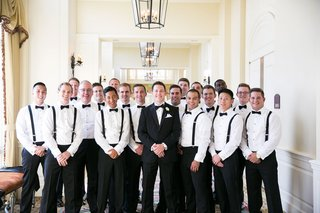 groom-in-tuxedo-with-groomsmen-in-black-pants-white-shirts-black-bow-ties-and-suspenders