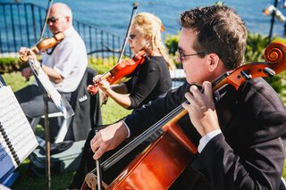 musicians-sit-near-the-ocean-adding-live-music-the-the-ceremony