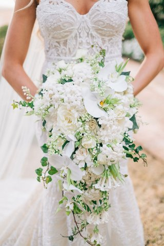 bride-in-berta-wedding-dress-holding-cascade-bouquet-cascading-with-white-orchid-flowers-greenery