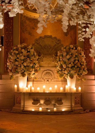 back-of-wedding-ceremony-ballroom-with-candles-and-flower-arrangements-orchids-branches