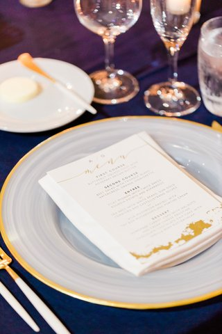wedding-menu-card-with-gold-calligraphy-on-white-charger-plate-with-gold-rim-matching-flatware-fork