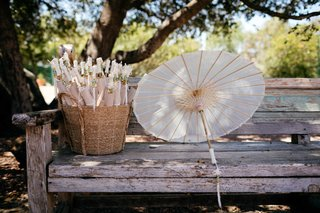 parasols-handed-out-to-guests-for-ceremony-on-wood-bench