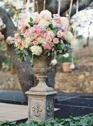 stone-urn-wedding-flower-arrangement-with-rose-and-hydrangea-flowers-in-purple-pale-blue-and-ivory