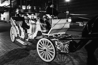 black-and-white-photo-of-bride-and-groom-in-horse-drawn-carriage-leaving-wedding