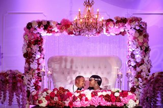 bride-in-glam-headband-with-groom-on-throne-sweetheart-table-arch-of-flowers-pink-fuchsia-lighting