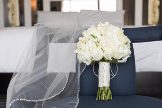 traditional-white-flower-bridal-bouquet-next-to-veil-with-crystal-border