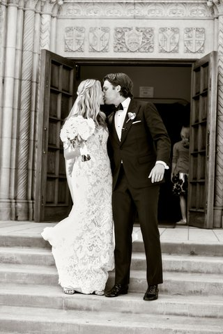 black-and-white-photo-of-bride-and-groom-leaving-church-doors-going-down-steps-kiss-after-ceremony