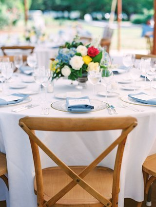wedding-reception-round-table-white-linen-blue-napkin-low-centerpiece-yellow-white-blue-red-flowers
