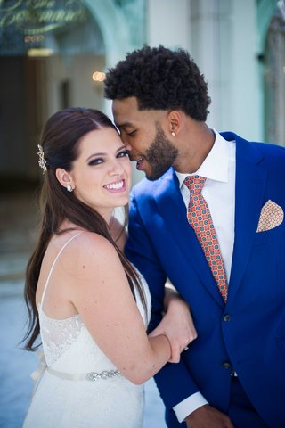 bride-in-white-wedding-gown-with-her-groom-in-bright-blue-tuxedo-orange-and-blue-tie-pocket-square