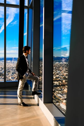 groom-in-mismatched-suit-grey-slacks-black-jacket-looks-out-high-rise-window-in-downtown-la