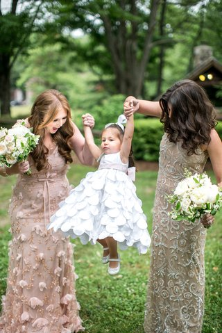 bridesmaids-in-mismatch-dresses-with-bouquets-holding-hands-with-flower-girl-white-flower-girl-dress