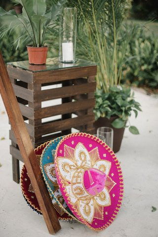 wedding-reception-photo-booth-set-up-wood-details-swing-on-sand-with-pink-magenta-and-blue-sombrero