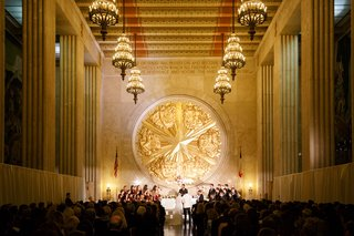 bride-and-groom-at-altar-gold-texas-emblem-chandeliers-overhead-hall-of-state-venue-in-texas-dallas