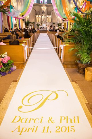personalized-monogram-aisle-runner-with-names-and-wedding-date-and-colorful-drapery-over-church-pews