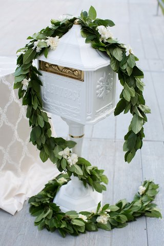 wedding-gift-box-area-garland-of-greenery-ivory-flowers-white-letter-box-gold-details-hardware
