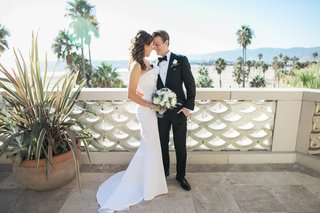 bride-in-j-mendel-wedding-dress-groom-in-suitsupply-suit-newlyweds-at-balcony-overlooking-beach