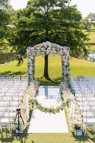 wedding-ceremony-outside-white-aisle-runner-shepherd-hook-flower-garland-flowers-along-aisle-arch