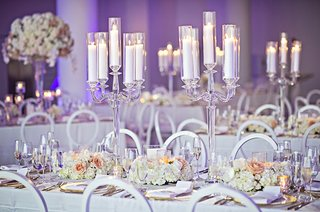 white-candles-in-crystal-candelabra-round-back-chairs-purple-uplighting