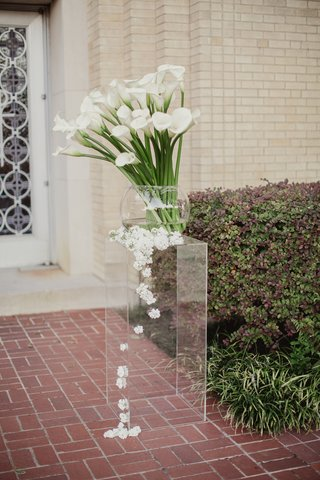 calla-lilies-on-long-stems-in-glass-bowl-white-blossoms-cascade-down-lucite-stand
