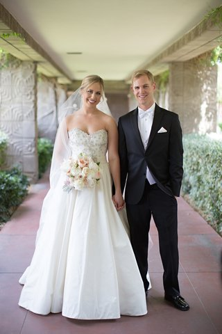 bride-in-anne-barge-ball-gown-and-veil-holds-hand-of-groom-in-black-tuxedo-at-arizona-biltmore