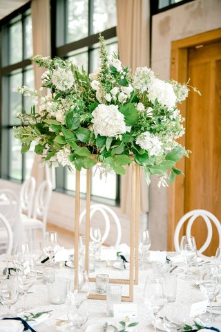 wedding-reception-centerpiece-gold-riser-greenery-leaves-white-flowers-candle-votives-velvet-ribbon