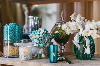 wood-shelf-with-blue-and-white-candies-in-glass-bowls-and-vessels-white-orchids