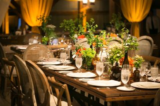 wood-table-with-no-runner-at-wedding-reception-and-greenery