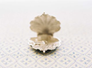 round-diamond-engagement-ring-with-square-halo-in-scallop-shell-jewelry-holder