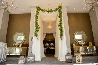 wedding-reception-entrance-tall-ceiling-drapery-garland-chandelier-two-mirrors-buffet-sideboard