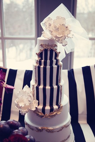 white-wedding-cake-with-black-stripes-golden-details-white-flowers-and-veil
