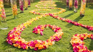 outdoor-wedding-aisle-with-orange-yellow-and-hot-pink-petal-swirls