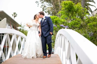 bride-in-allure-ball-gown-groom-in-navy-joseph-abboud-suit-kiss-on-bridge-over-venice-canals