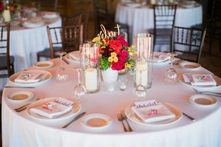 a-simple-white-tablescape-on-round-table-with-small-floral-arrangement-red-yellow-pink-flowers