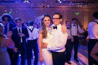 wedding-reception-purple-pink-lighting-bride-in-second-wedding-dress-groom-in-white-shirt-bow-tie