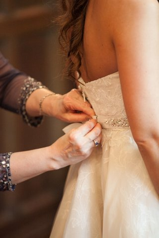a-bride-gets-helps-getting-zipped-into-her-wedding-gown-before-her-church-ceremony