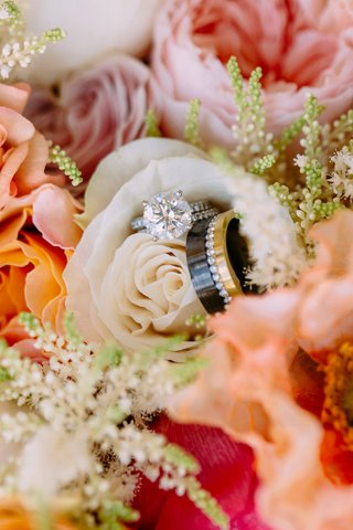 bridal-bouquet-white-pink-orange-flowers-round-solitaire-engagement-ring-mens-band-black-gold